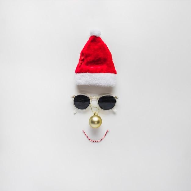 サンタの帽子とサングラスからの顔のクリスマスの組成 無料写真