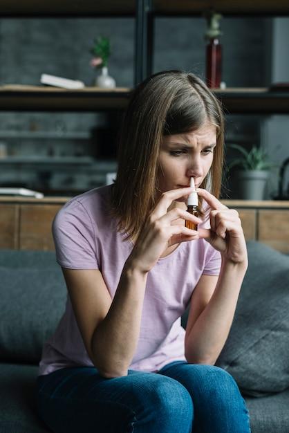 Больная женщина, обнюхивающая носовой спрей Бесплатные Фотографии