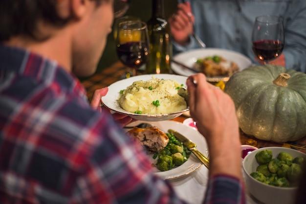 Человек, держащий табличку за столом с едой Бесплатные Фотографии
