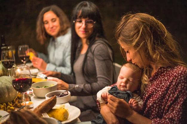 家族の夕食に小さな赤ちゃんにキスする母 無料写真