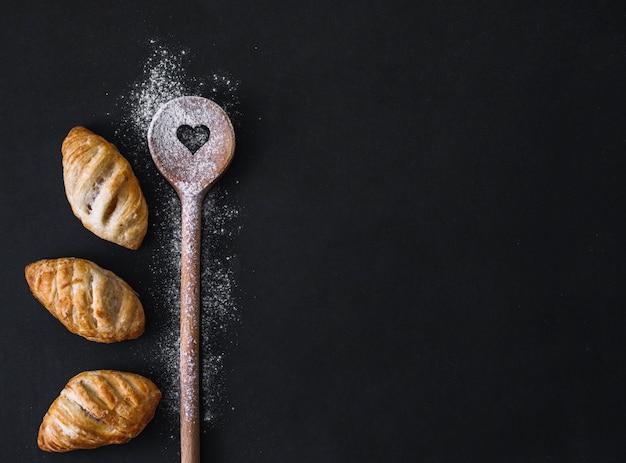 Повышенный вид свежих круассанов; ложка в виде муки и сердечка на черной поверхности Бесплатные Фотографии