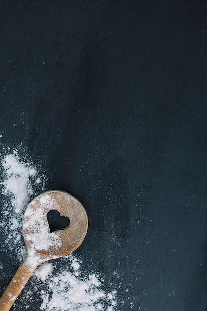 黒い表面上のハート形のスプーンと小麦粉の高さのビュー 無料写真