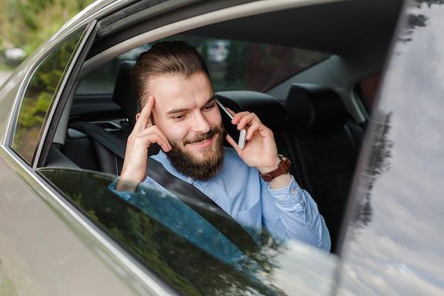 スマートフォンで話す車の中に座っている幸せな男 無料写真