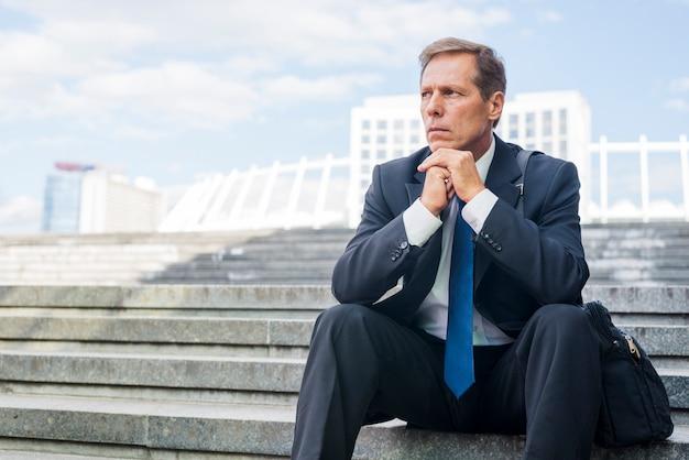 深刻な成熟したビジネスマン、階段に座っている 無料写真