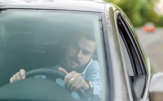 フロントガラスから見て携帯電話で話す車の中に座っている男 無料写真