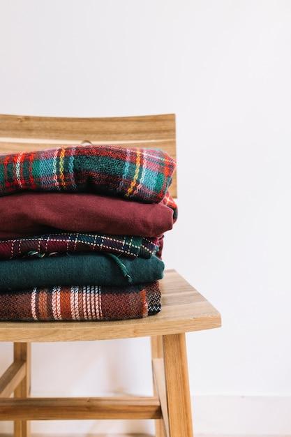 木製の椅子のクリスマスのセーターの山 無料写真