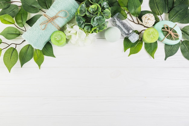 木製の表面に緑の葉で飾られたスパ製品 無料写真