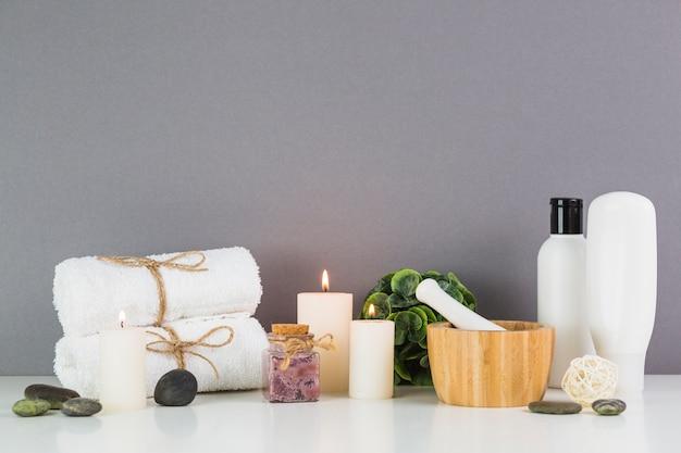 Горящие свечи и косметика перед серой стеной Бесплатные Фотографии