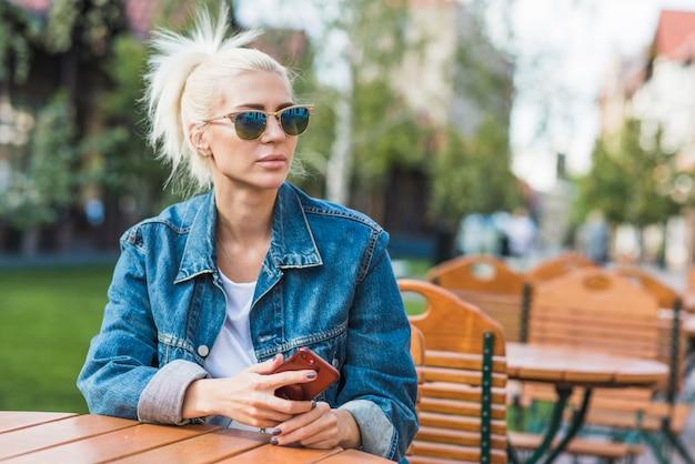 屋外のカフェに座っているスマートフォンで美しい若い女性 無料写真