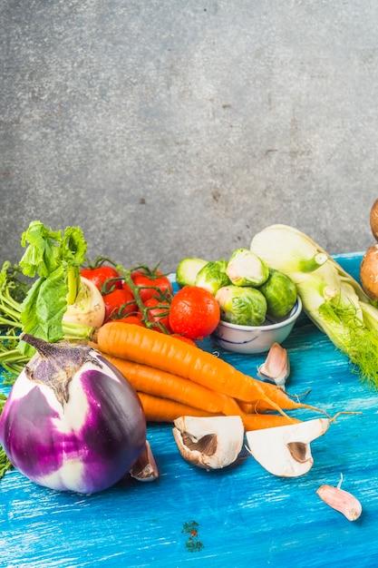 青い木製の表面に様々な新鮮な有機野菜 無料写真