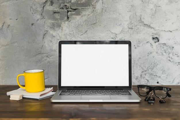 木製のテーブルにオフィス用品と黄色のコーヒーマグと開いたラップトップ 無料写真