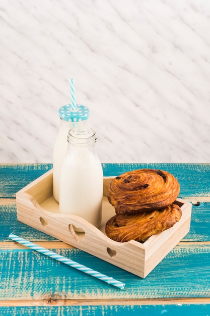 デンマークのペストリー、ミルクボトル、木製のトレイ、ストローの近く、青い木製のテーブル 無料写真