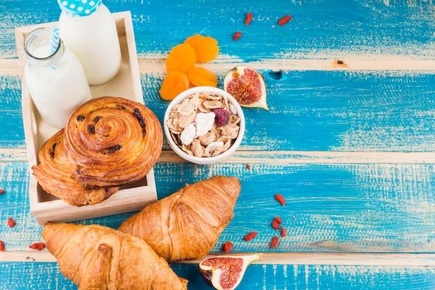 Запеченная еда с молочными бутылками; кукурузные хлопья; инжир и курага на синей деревянной доске Бесплатные Фотографии
