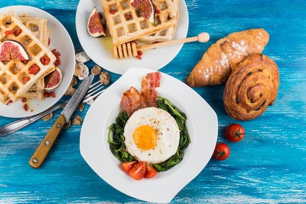 イチジクとワッフル;焼きたてのペストリーと卵の揚げた卵、青いテクスチャの背景に白いプレートに 無料写真