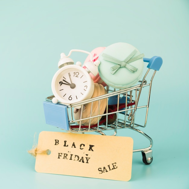 ショッピングカートの近くに目覚まし時計とマカロンが付いたショッピングトロリー 無料写真
