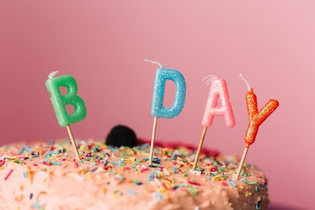 色とりどりの背景にケーキの誕生日のろうそく 無料写真