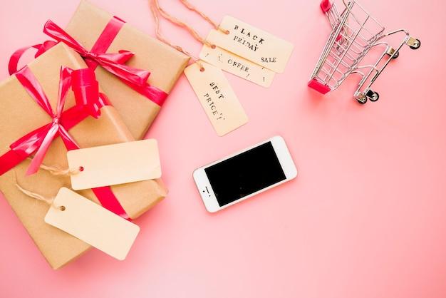 Смартфон рядом с магазинной тележкой и настоящими коробками Бесплатные Фотографии