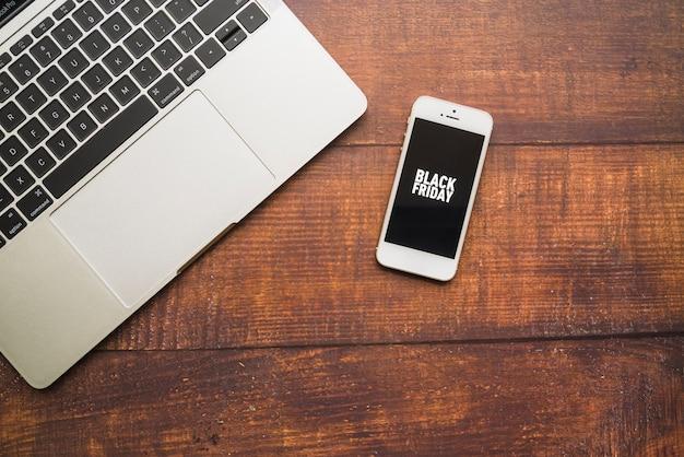 木製ボード上のラップトップに近いスマートフォン 無料写真