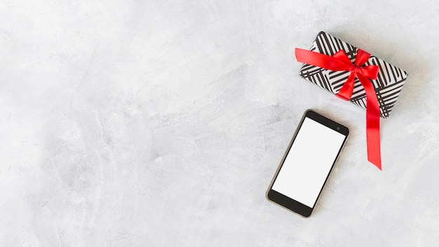 テーブルにギフトボックスを備えたスマートフォン 無料写真