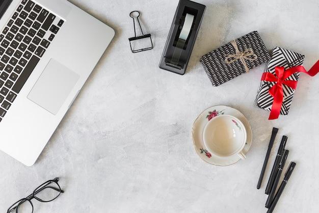 プレゼントボックスの近くにノートパソコン、皿と文房具にカップ 無料写真