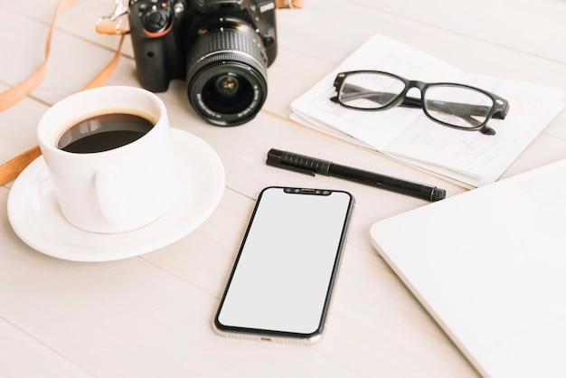 コーヒーカップ;カメラ;携帯電話;ペン;木製のテーブル上のノートブックの眼鏡 無料写真