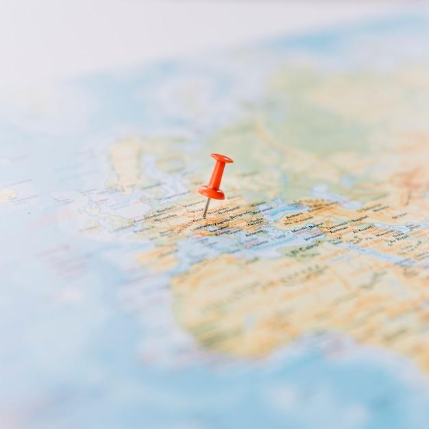 Крупный план красного пальца на карте мира расфокусированным Бесплатные Фотографии