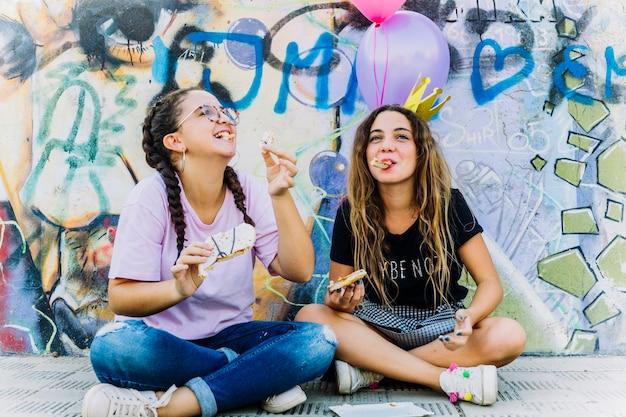 風船と誕生日のペストリーを持つお友達と座る 無料写真