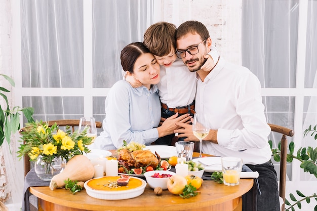 お祝いのテーブルで両親を抱擁している少年 無料写真