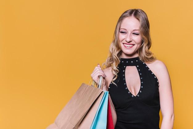 ショッピングバッグを着たドレスの女性を笑う 無料写真