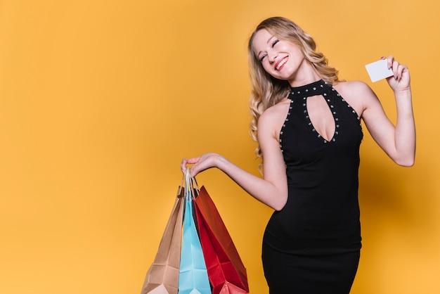 バッグとカードを持つ明るいショッピングの女性 無料写真