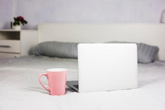 白いベッドとラップトップのコーヒーカップ 無料写真