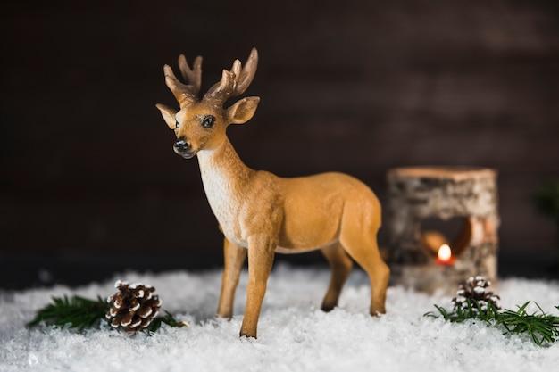 おもちゃの鹿は雪の上に枝や小枝の近くに 無料写真