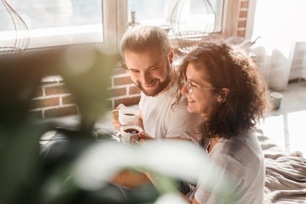 手でコーヒーのカップを保持している笑顔の若いカップルを愛する 無料写真