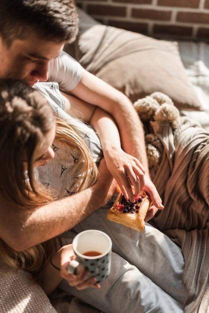 果実とコーヒーカップとペストリーを保持しているベッドに横になっているカップルの俯瞰 無料写真