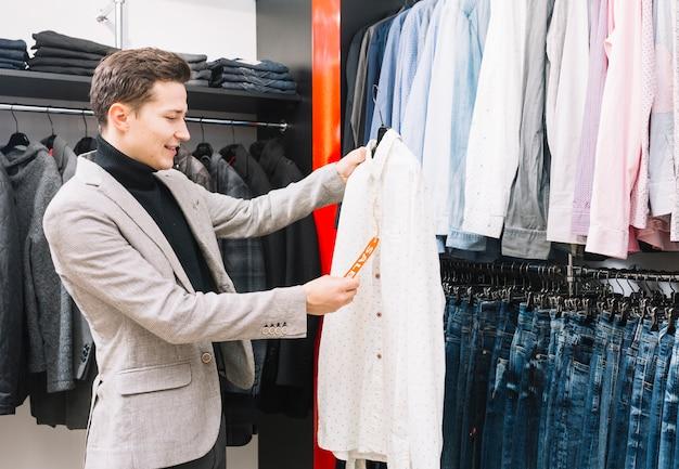 シャツの値札をチェックしている店の若い男 無料写真
