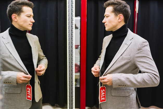 店のジャケットを試している鏡の前に立っている男 無料写真
