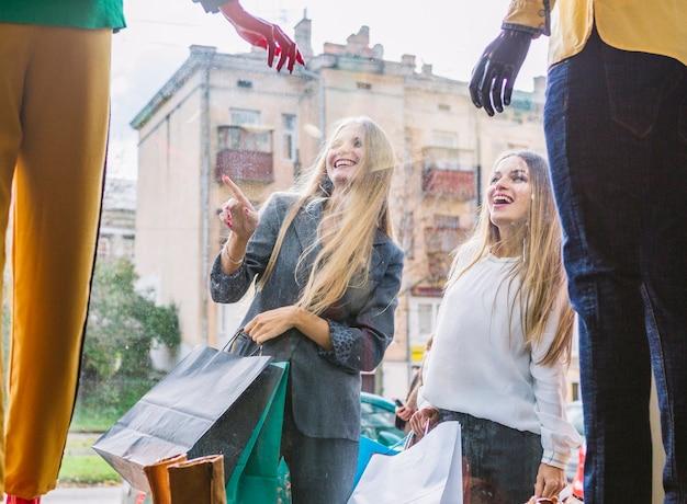 ウィンドウ表示で店の外に人差し指で立っている女性 無料写真