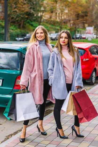 路上でポーズをとって多くのカラフルな買い物袋を保持しているスタイリッシュな若い女性 無料写真