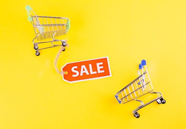 黄色の背景に販売タグ付きミニチュア空っぽのショッピングカート 無料写真
