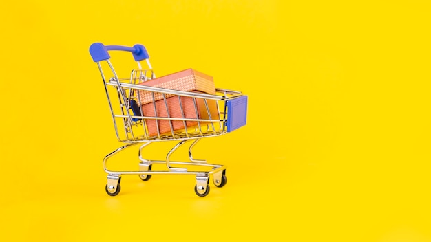 Розовая подарочная коробка в миниатюрной корзине на желтом фоне Бесплатные Фотографии