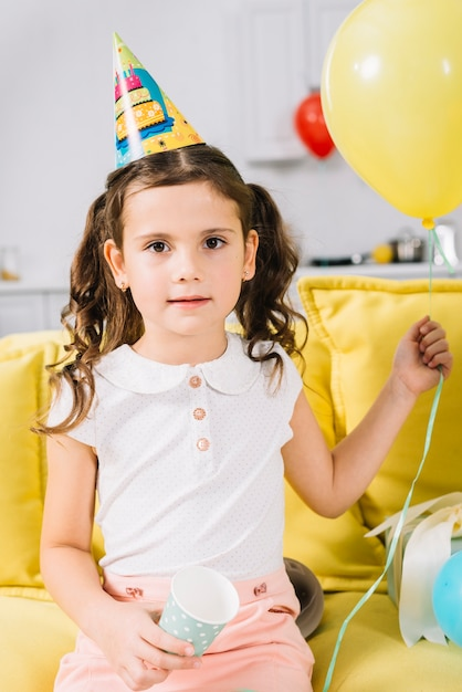 バルーンを手に持ってソファーに座っていた少女の肖像画 無料写真