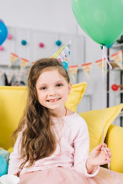 彼女の手に緑色の風船を持ってソファーに座って微笑んでいる女の子の肖像画 無料写真