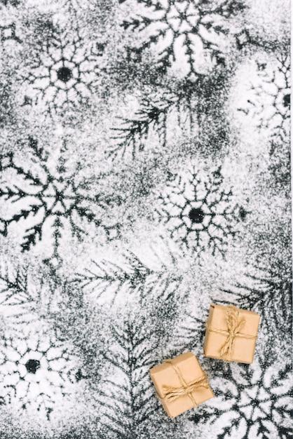 粉状の砂糖の雪の上に小さなプレゼント 無料写真