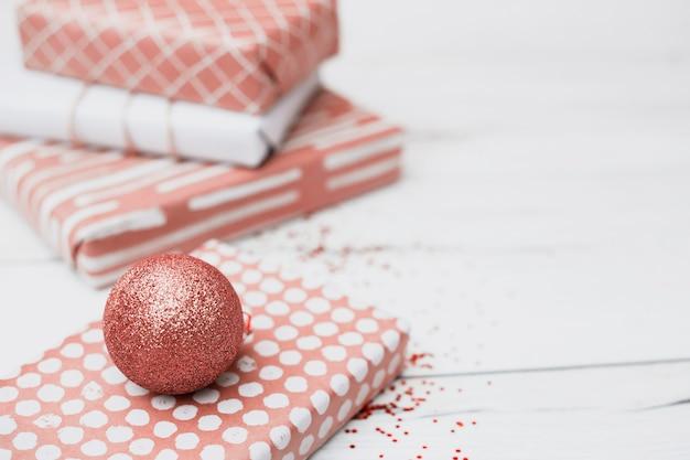 クリスマスボールの近くのラップでプレゼント 無料写真
