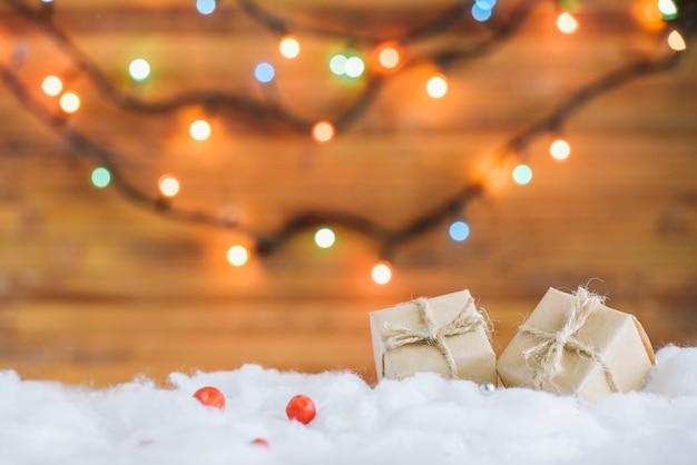 Подарочные коробки на декоративном снегу возле сказочных огней Бесплатные Фотографии