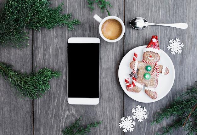 飲み物、雪片、小枝のカップの近くのプレートにビスケット雪だるまに近いスマートフォン 無料写真