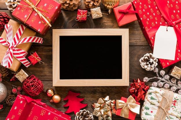 ギフトボックスとクリスマスの装飾のセットの間のフォトフレーム 無料写真