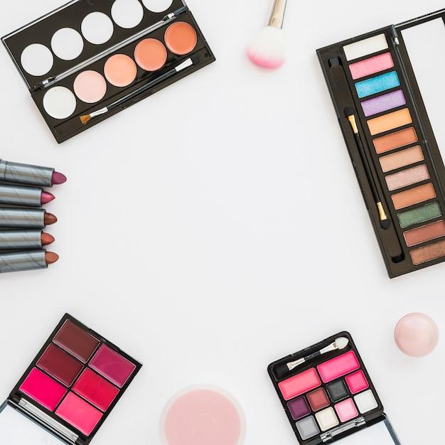 Различный тип красочной палитры для макияжа с помадой; губка и компактная пудра на белом фоне Бесплатные Фотографии