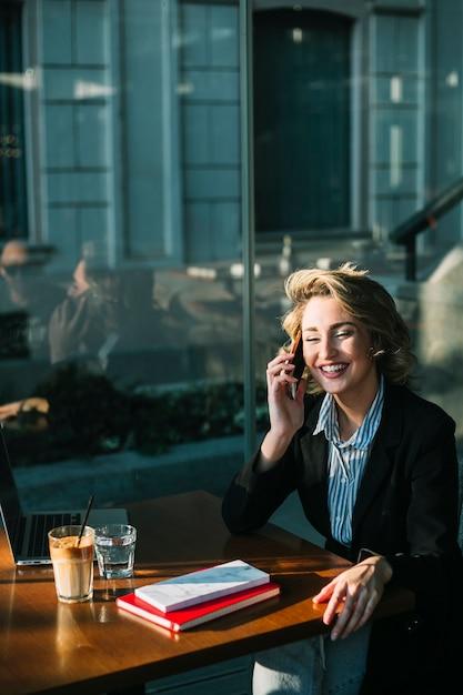 Счастливая коммерсантка сидя в ресторане используя мобильный телефон Бесплатные Фотографии