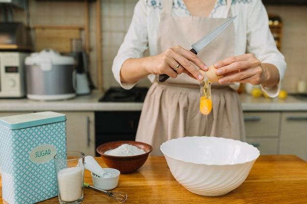 女性が台所でパイを作るための卵を破る 無料写真
